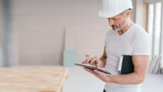 Handwerker erfasst seine Arbeitszeiten am Tablet.